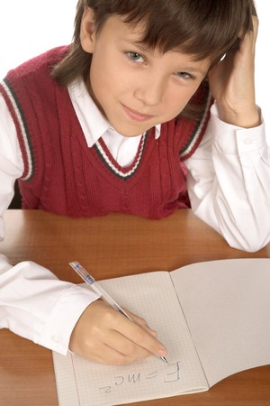 formulation: young schoolboy writing formula in the  notebook