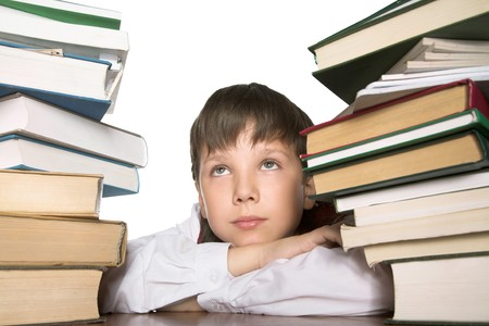 Schoolboy sitting at the table pilled up with books photo