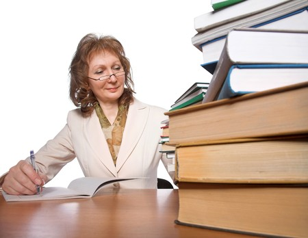 mature woman sitting at the table with big books photo