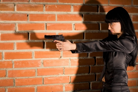 Young woman with hand gun near brick wall photo