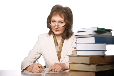 mature woman sitting at the table with big books Stock Photo - 8696770