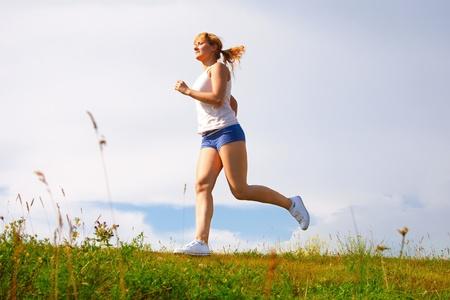 young happy girl running on sunny meadow photo