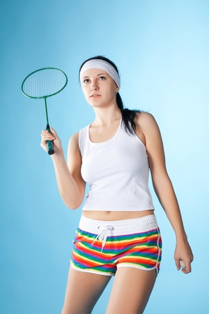 beauty woman with badminton racket isolated on blue photo