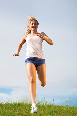 adults only: young happy girl running on sunny meadow Stock Photo
