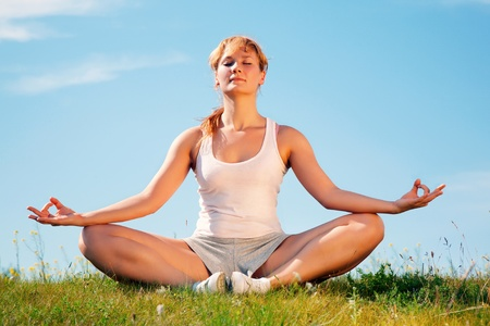 young happy girl training yoga on sunny meadow Stock Photo - 8773858