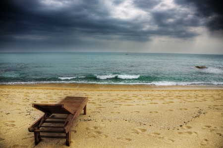 thunderstorm: a lonely lounger on the stormy beach