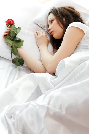 red pillows: young beauty girl lying in the bed
