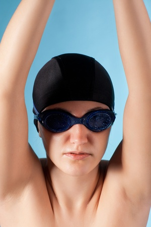 young beauty swimmer isolated on blue background photo
