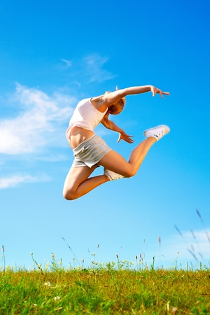 woman relax: young happy girl jumping on sunny meadow Stock Photo