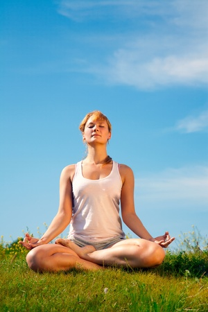 young happy girl training yoga on sunny meadow Stock Photo - 8886652