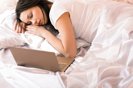 gente durmiendo: joven belleza de port�til acostado en la cama