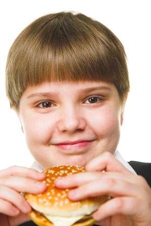 fun young fat schoolboy eating big hamburger photo