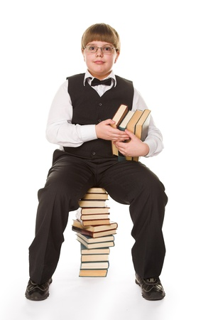 pensiveness: young schoolboy with books isolated on white