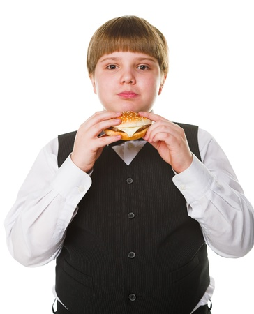 obese child: happy schoolboy with big burger isolated on white
