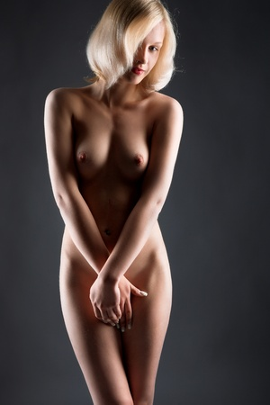 shy nude girl isolated on gray background