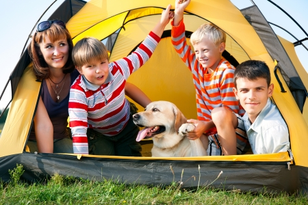 happy family in the tent on sunny meadow photo
