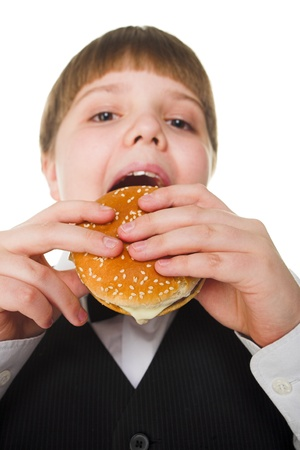 Young fat school boy eating big hamburger photo