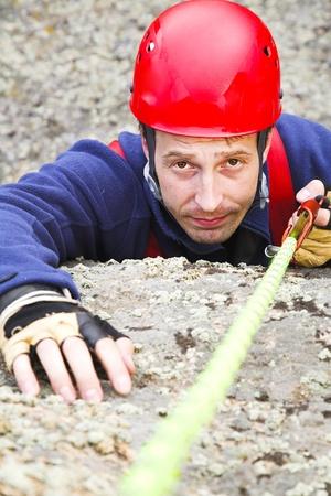 casco rojo: escalador de hombre en casco rojo con cuerda