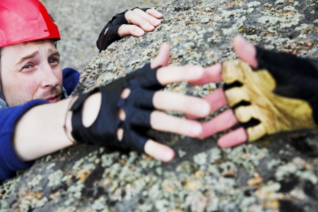 climbing sport: climber in red helmet reach out for help