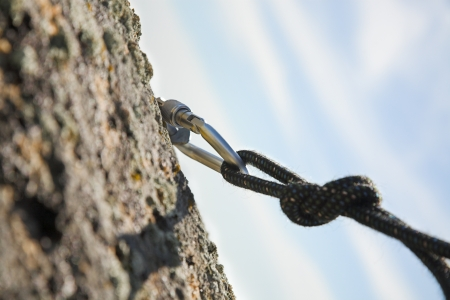 climbing iron with carabiner and rope on rock