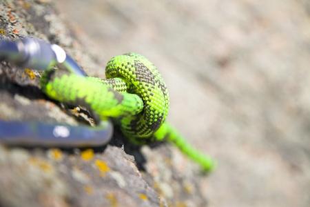 carabiner: climbers carabiner and loop of green rope