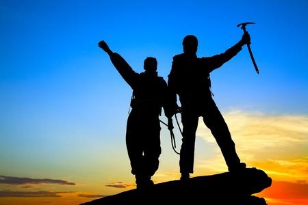 bergbeklimmen: Twee silhouetten van klimmers op de bergtop Stockfoto