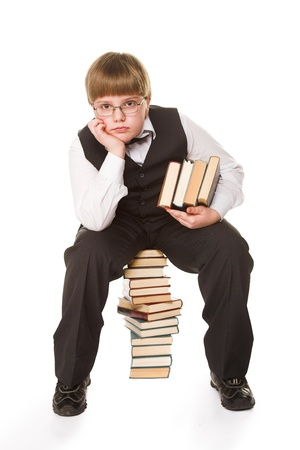 young schoolboy with books isolated on white photo