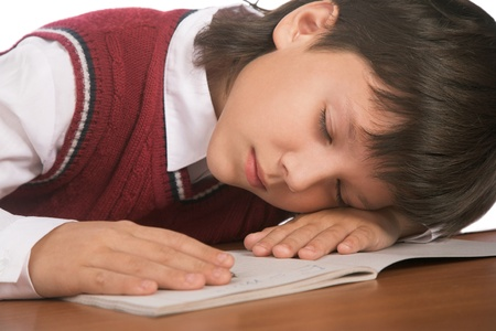 schoolboy sleeping on the table with notebook photo