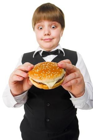 fun young fat schoolboy eating big hamburger
