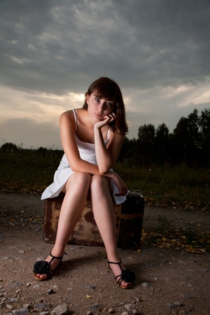 young woman outdoor sitting with her luggage  photo