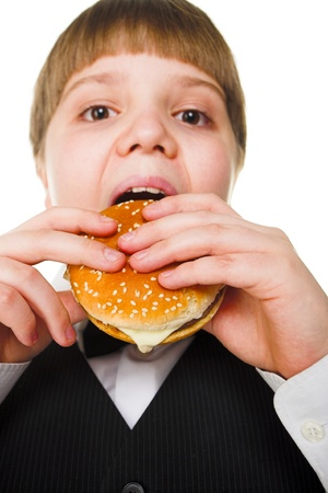 obese child: fun young fat schoolboy eating big hamburger  Stock Photo