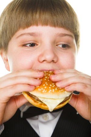 young fat schoolboy eating a big hamburger