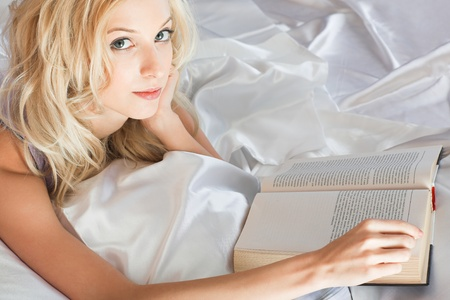 beauty girl with book in the bed photo