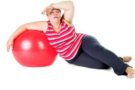 mujer gorda: mujer cansada de grasa con gran bola de gimnasia de color rojo Foto de archivo