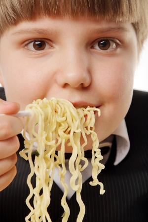 instant noodles: boy eating chinese instant noodles isolated on white Stock Photo
