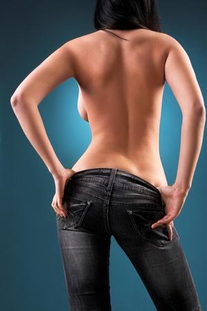 young nude girl: Frau steht wieder auf blauem Hintergrund cyan Lizenzfreie Bilder
