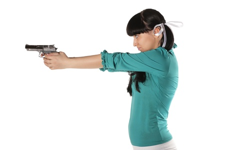 fashion shoot: Young woman with hand gun isolated on white Stock Photo