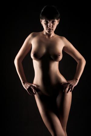 donne nude: giovani donne nude su sfondo nero Archivio Fotografico