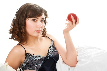 bedsheet: Portrait of young woman laying on bed eating apple