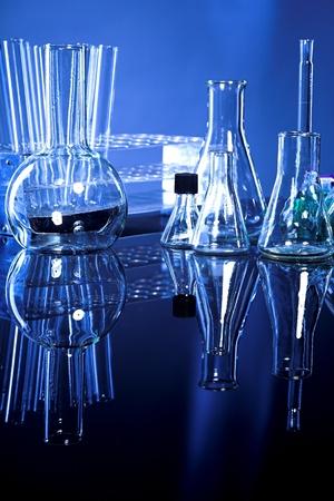 material de vidrio: Cristaler�a de laboratorio sobre fondo azul marino con el reflejo en la mesa