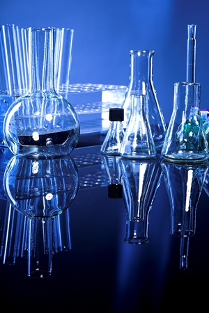 Laboratory glassware on navy-blue background with reflex on table Stock Photo