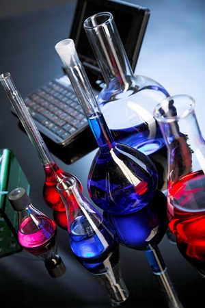 material de vidrio: Cristaler�a de laboratorio sobre fondo azul con reflejo en la mesa