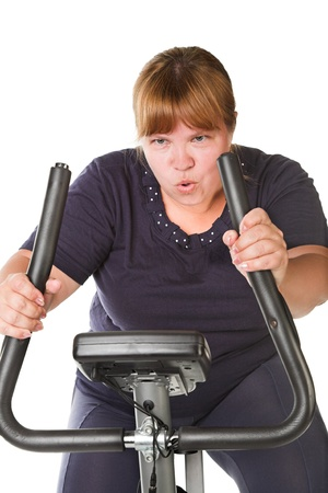 tired fat woman training on the bike Stock Photo