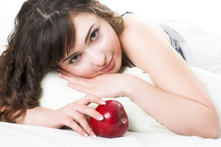 Portrait of young woman laying on bed eating apple photo