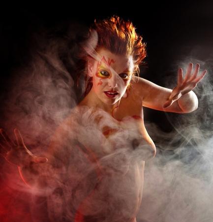 schöne Frau mit Make-up und auf einem schwarzen Hintergrund Rauch