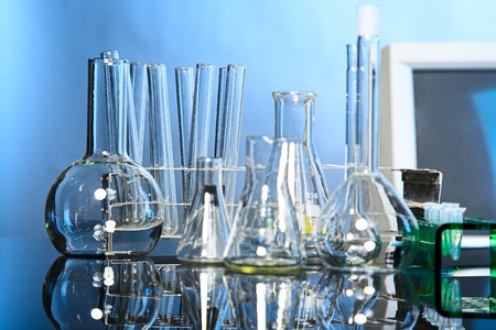 Laboratory glassware on blue background with reflex on table photo