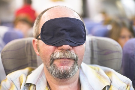 manture man in sleeping mask in the airplane photo