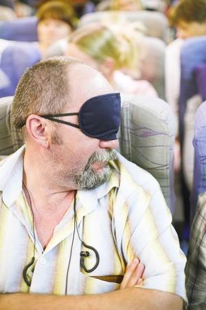 manture man in sleeping mask in the airplane