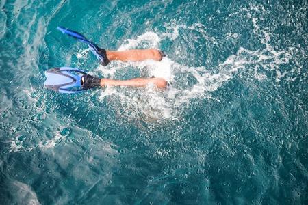 agachado: patas en aletas de buceo en el mar azul Foto de archivo