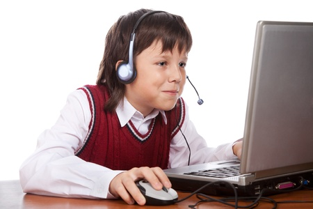 young boy in headset playing with laptop photo